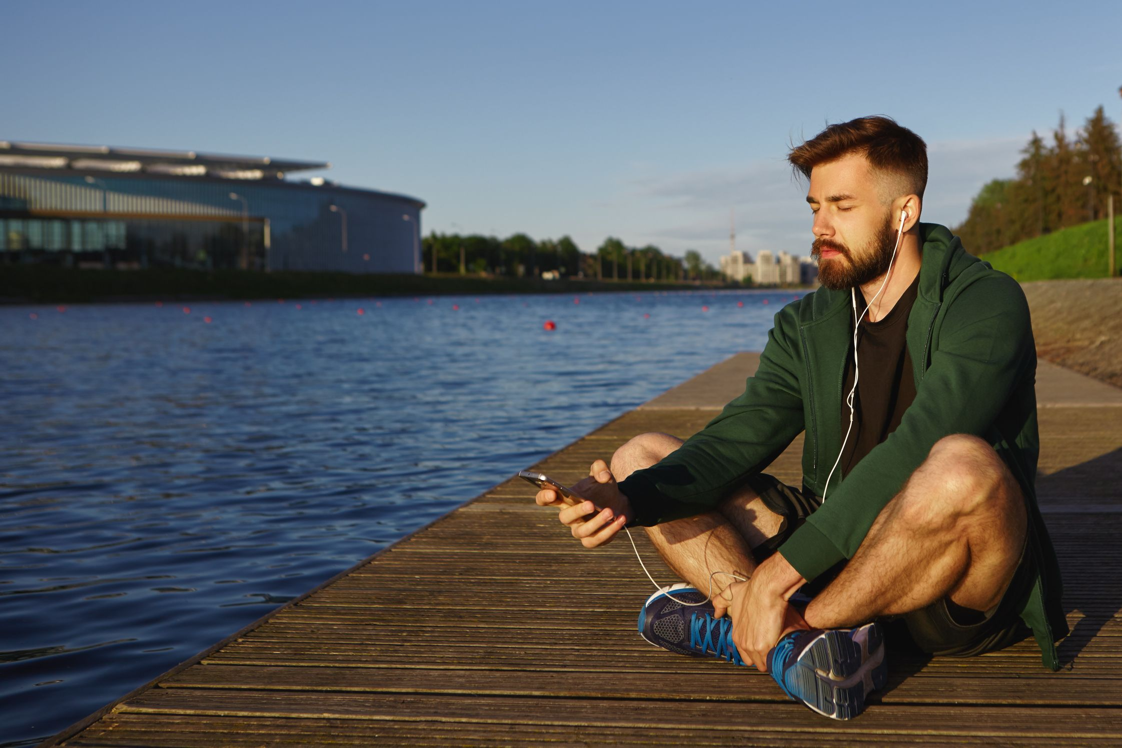 outdoor shot handsome unshaven young guy with stubble spending peaceful summer morning alone by lake sitting with eyes closed listening meditative music tracks modern smart phone